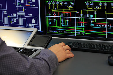 image of a mans hand at a desk in front of two SCADA screens monitoring industrial processes