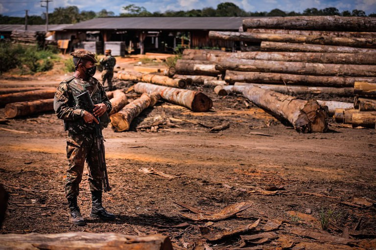 A foto mostra um homem usando uma farda do exército brasileiro, de máscara e segurando uma arma de fogo parado em pé. Atrás dele se vê troncos de árvores cortados e empilhados próximo a um galpão.