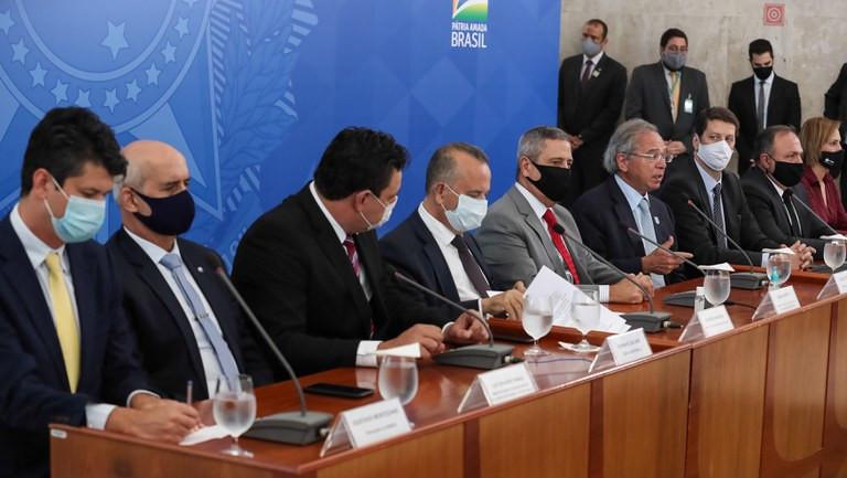 É uma foto tirada levemente na lateral. Ela mostra homens usando ternos e máscaras, sentados em uma mesa comprida numa reunião governamental.