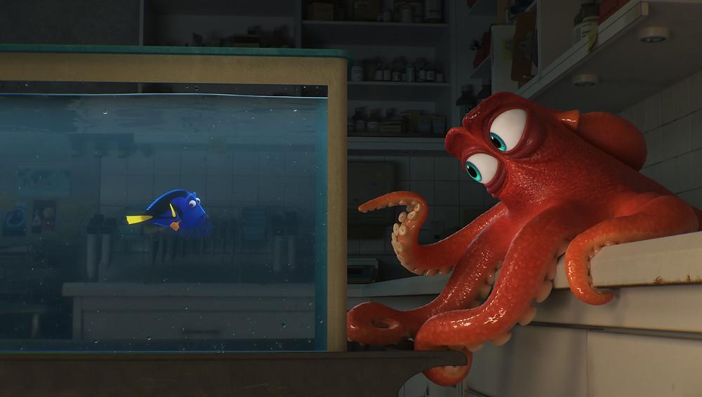 A foto mostra uma cena do filme. O peixe azul e de cauda amarela Dory está dentro do aquário e ela conversa com o polvo Hank. O polvo está fora do aquário, apoiado em uma bancada. Ele é vermelho e tem olhos azuis.