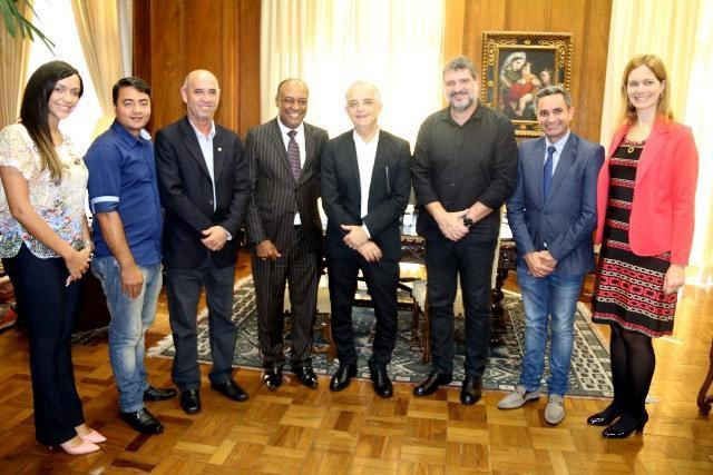 A foto mostra oito pessoas em pé em uma sala sorrindo para a foto. Da esquerda para a direita: uma mulher branca, cabelo liso e castanho escuro, usa uma blusa estampada e calça jeans; um homem branco, cabelo curto, camisa azul e calça jeans; um homem branco, careca, usa terno preto; um homem negro, calvo, usa terno preto; um homem branco, calvo e cabelos brancos, usa terno preto; um homem branco, com barba grisalha, cabelo grisalho, usa camisa e calça preta; um homem branco, cabelo castanho, paletó azul e calça jeans; e uma mulher branca, cabelo liso claro, usa vestido preto com listras vermelhas.