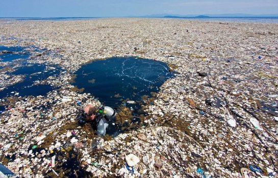 A foto mostra uma grossa camada de lixo cobrindo o oceano. No meio dela um mergulhador atravessa o lixo.