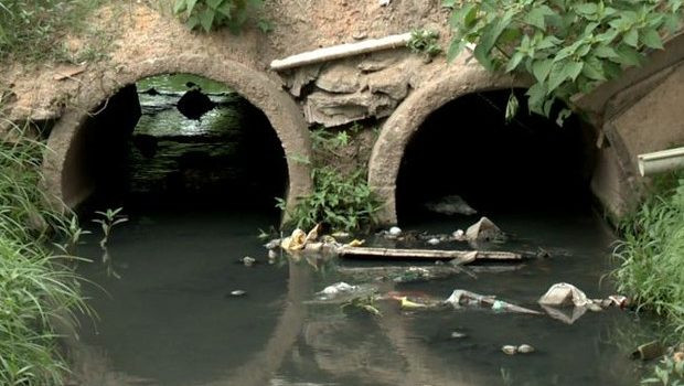 A foto mostra um córrego com dois bueiros cheios de água escura e lixo boiando.