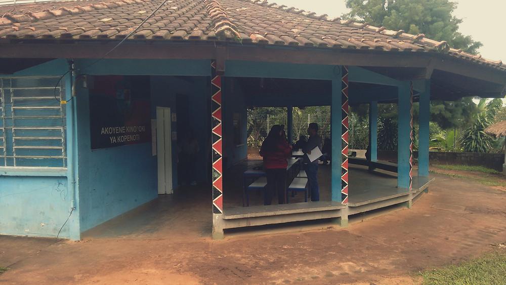 A foto mostra uma construção com paredes azuis e pilares coloridos com preto e vermelho. Pessoas conversam no pátio.