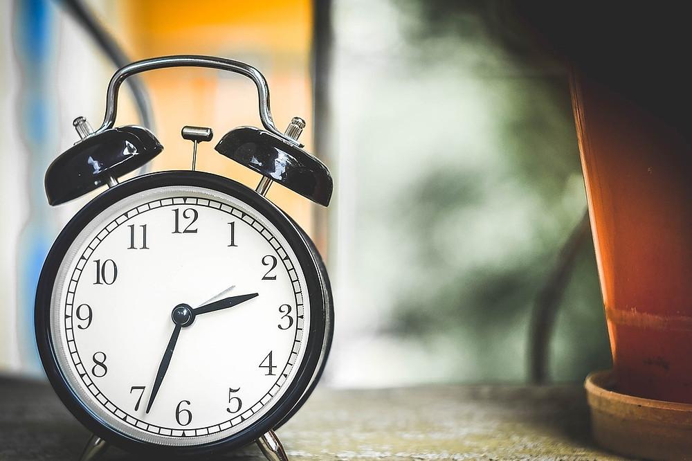 A foto mostra um relógio redondo de ponteiros indicando ser 02 horas e 34 minutos.