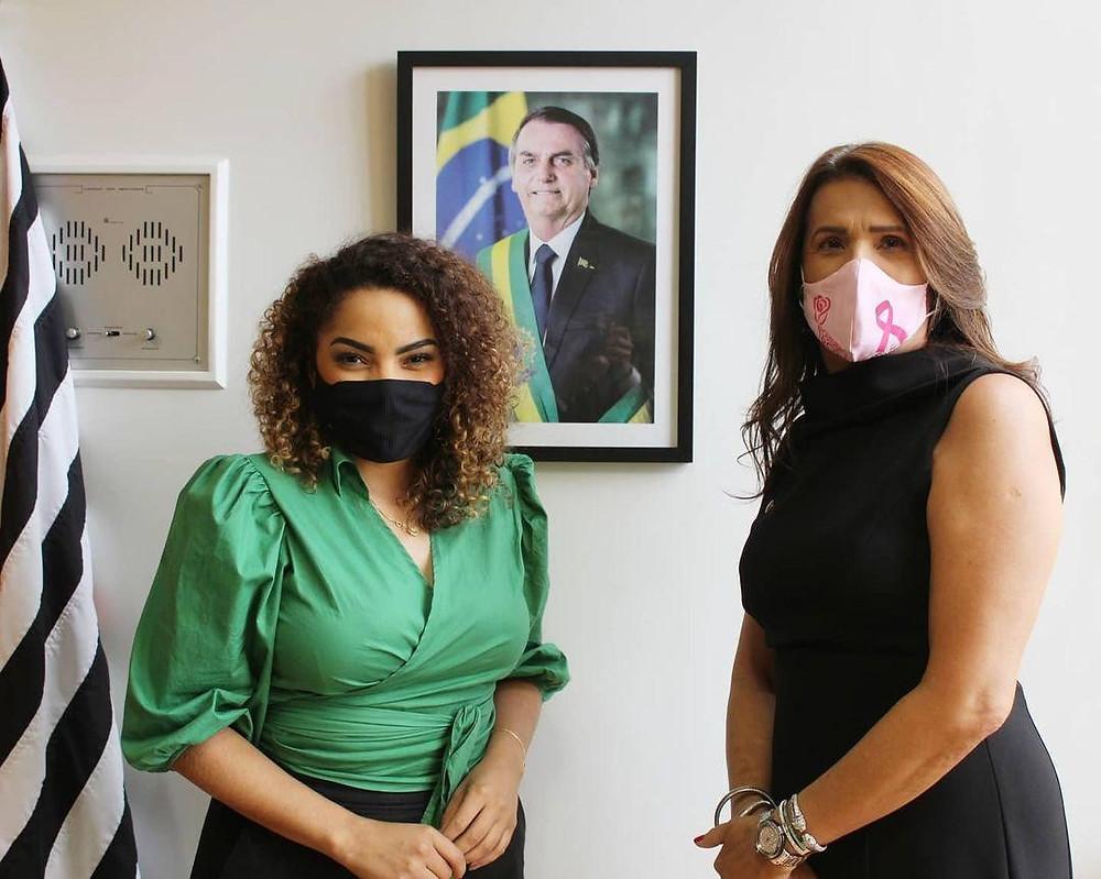 A foto mostra Suéllen Rosim e Valéria Bolsonaro. Suéllen está à esquerda, ela é uma mulher negra, cabelo cacheado castanho com pontas loiras, ela usa uma máscara preta e usa uma blusa verde lisa com mangas até o cotovelo. Valéria está à direita, ela é uma mulher branca, com cabelo liso castanho claro, ela usa um vestido preto colado e usa uma máscara rosa. No meio das duas tem uma quadro do presidente Jair Bolsonaro na parede.