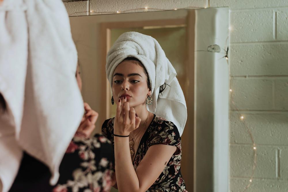 É uma foto. Ela mostra uma mulher na frente do espelho passando batom com os dedos. Ela é branca, sobrancelhas castanhas, usa brinco, uma blusa de manga curta florida e uma pulseira. Ela também usa uma toalha branca na cabeça.