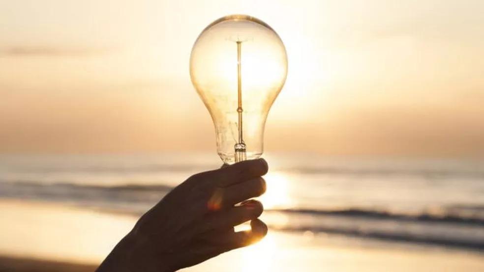 A foto mostra uma mão segurando uma lâmpada transparente e atrás tem o oceano no pôr do sol.