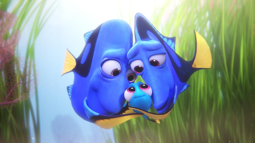 É uma cena do filme. Ela mostra os pais da Dory a abraçando. O peixe pai está à esquerda, Dory no meio e o peixe mãe está à direita. São azuis e caudas amarelas. Estão dentro da água com algas em volta.