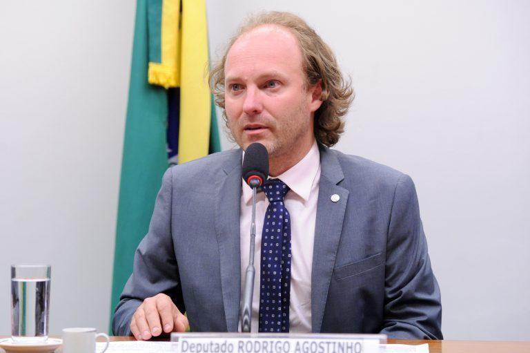A foto mostra o deputado Rodrigo Agostinho. Ele está sentado, apoiado em sua mesa com um microfone, ele é branco, olhos verdes claro, é calvo, e o cabelo é loiro jogado para trás. Ele usa um terno azul claro, com uma gravata azul escuro com bolinhas brancas. Ao fundo tem uma bandeira do Brasil.