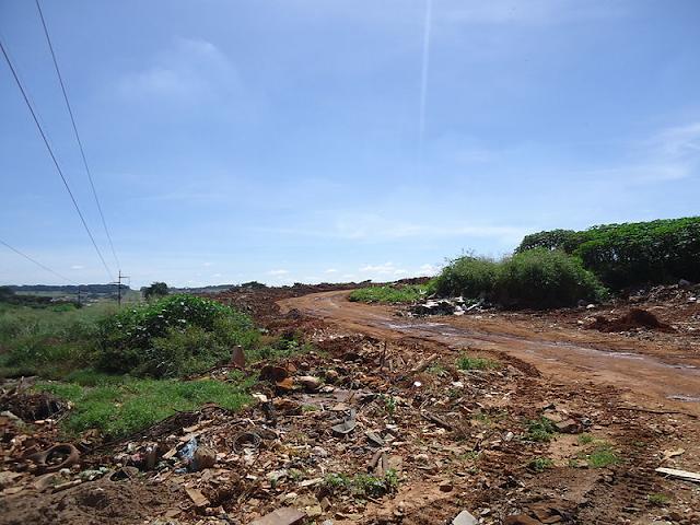 A foto mostra um terreno com grama verde e uma grande quantidade de lixo jogada nele, tem uma estradinha que leva até esse terreno. Ao fundo, o céu está azul e ensolarado com fios de energia a mostra.