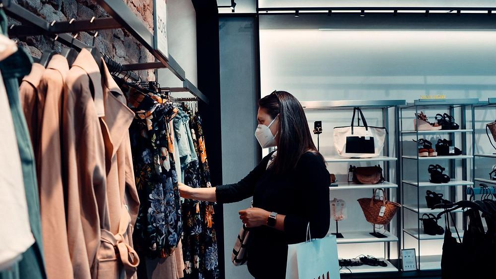 A foto mostra uma mulher de cabelo preto, liso e comprido, ela usa uma máscara N95 branca, uma blusa preta até o meio do braço, carrega uma sacola branca no braço. Ela está de perfil olhando uma arara de roupas em uma loja. No fundo tem prateleiras com bolsas e sapatos.