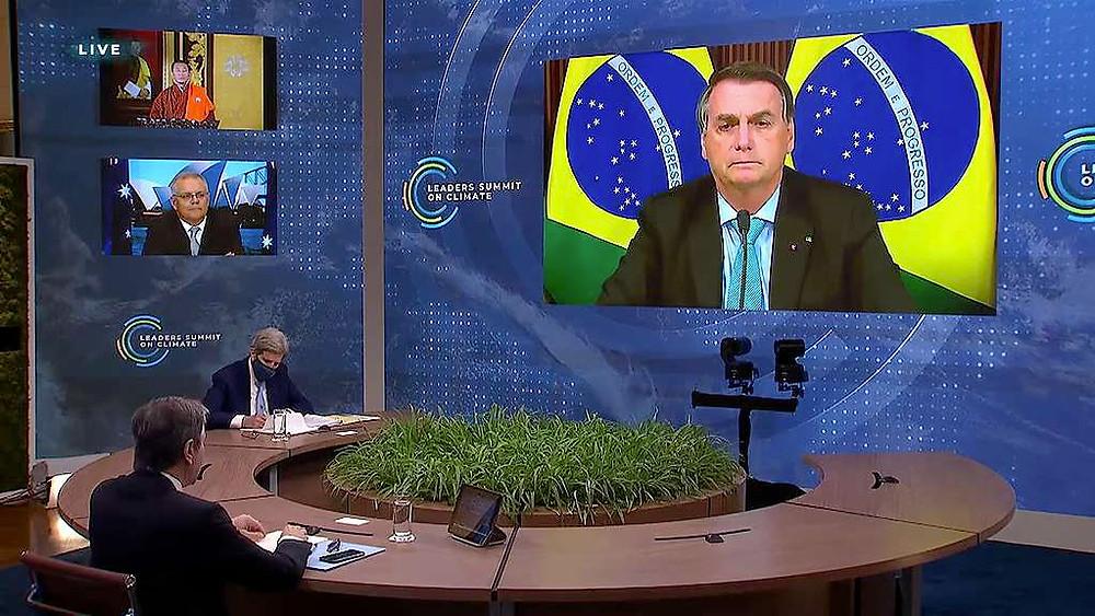 É uma fotografia. Ela mostra o presidente Bolsonaro num telão conversando com líderes mundiais em uma mesa redonda. No lado direito, tem mais dois telões que mostra jornalistas assistindo o pronunciamento do presidente.