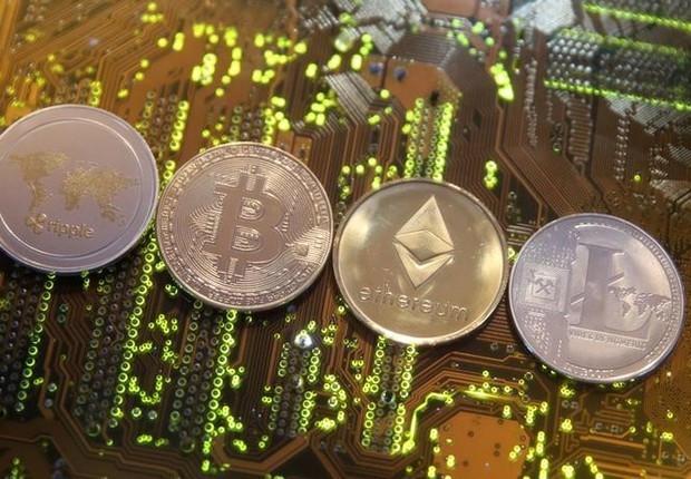 A foto mostra quatro moedas de bitcoin em cima de uma placa eletrônica. As moedas são de um metal dourado claro.