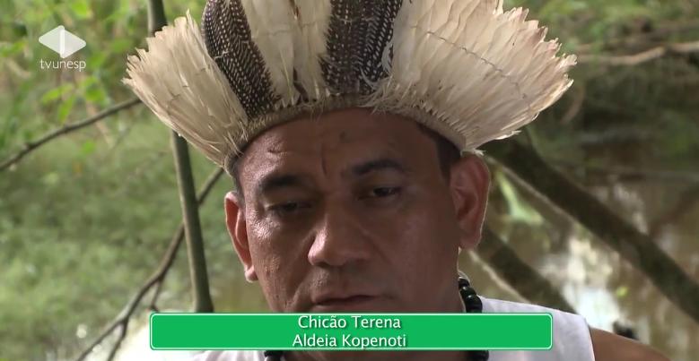A foto mostra um homem indígena de meia idade usando um cocar.