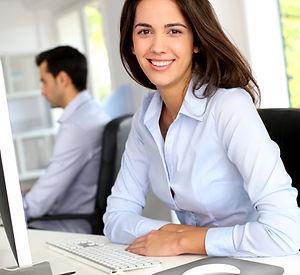 Smiling office worker in front of desktop computer