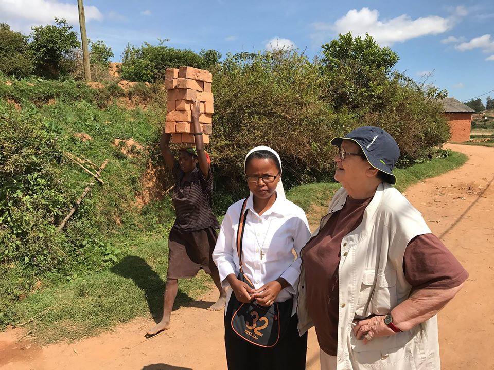 Une jeune femme portant des briques pour moins d'un €uro/jour, soeur Rolande et Francine.