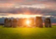 druide devant mégalithique au levé du soleil lumière mauve, jaune et blanche