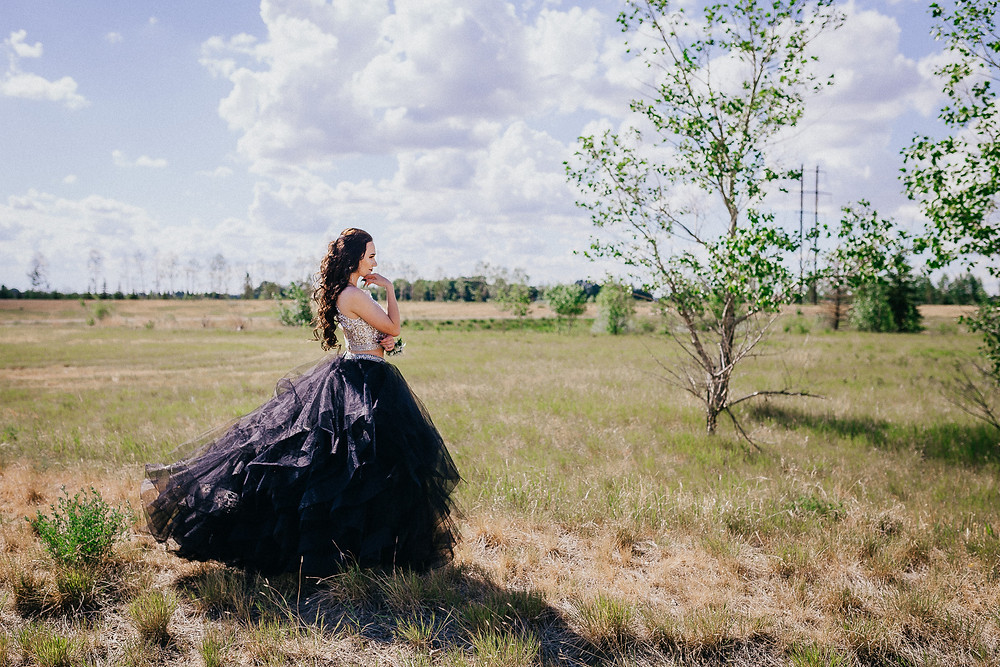 Beautiful graduate in two-piece, sequin and black tulle grad dress, posed and looking at trees in prairie field.