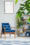 Navy blue armchair and plants in grey fl
