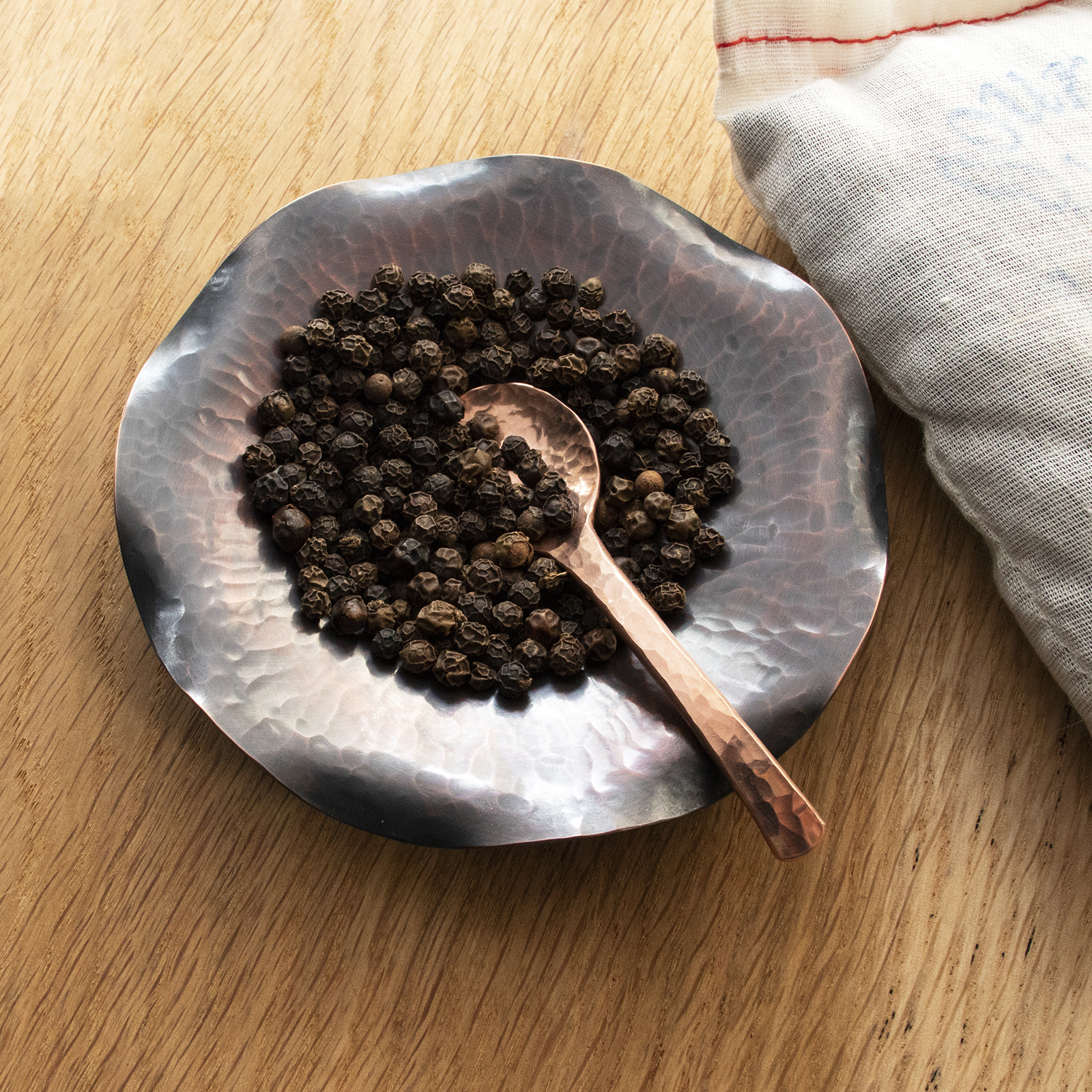Salt spoon in dark dish with peppercorn