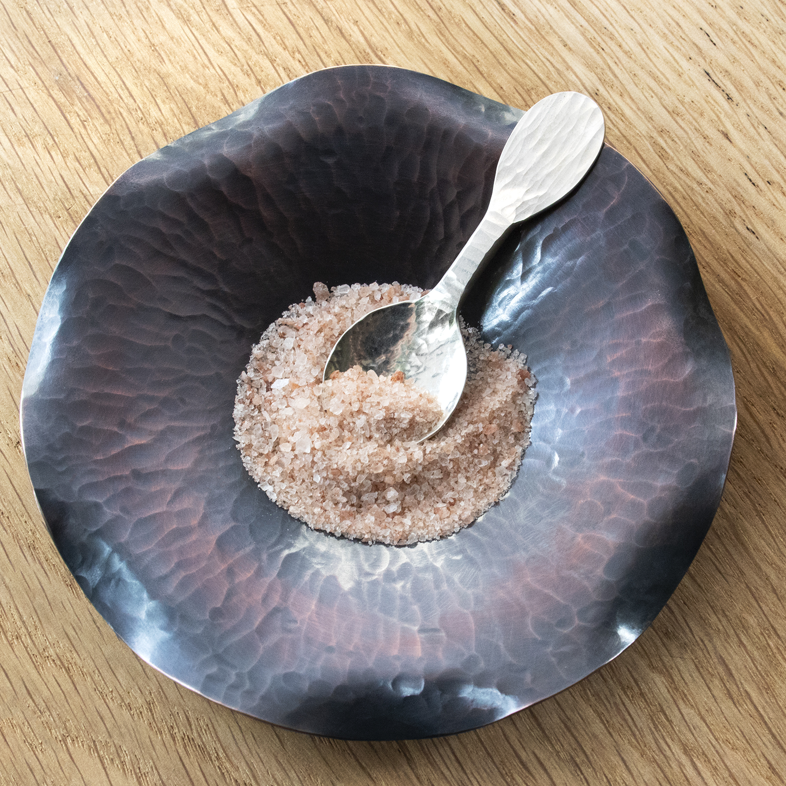SS tasting spoon in dark dish with salt