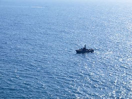 Navy patrol boat in action with blue oce