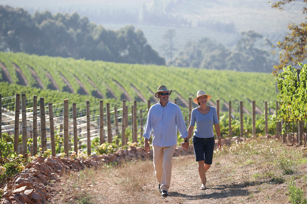 Older couple walking through a vineyard. When you purchase wine through you are helping small vineyards out.