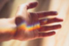 main ourant sur un rayon arc-en-ciel