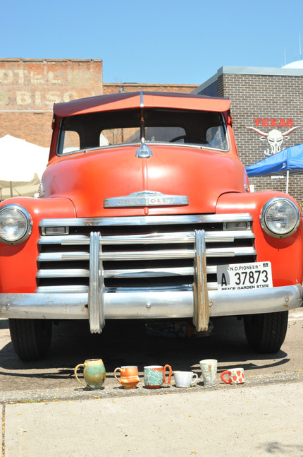Mugs in front of the iconic Red River Market truck