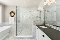Master bathroom in new luxury home_ Bathtub and shower with tile and glass shower doors