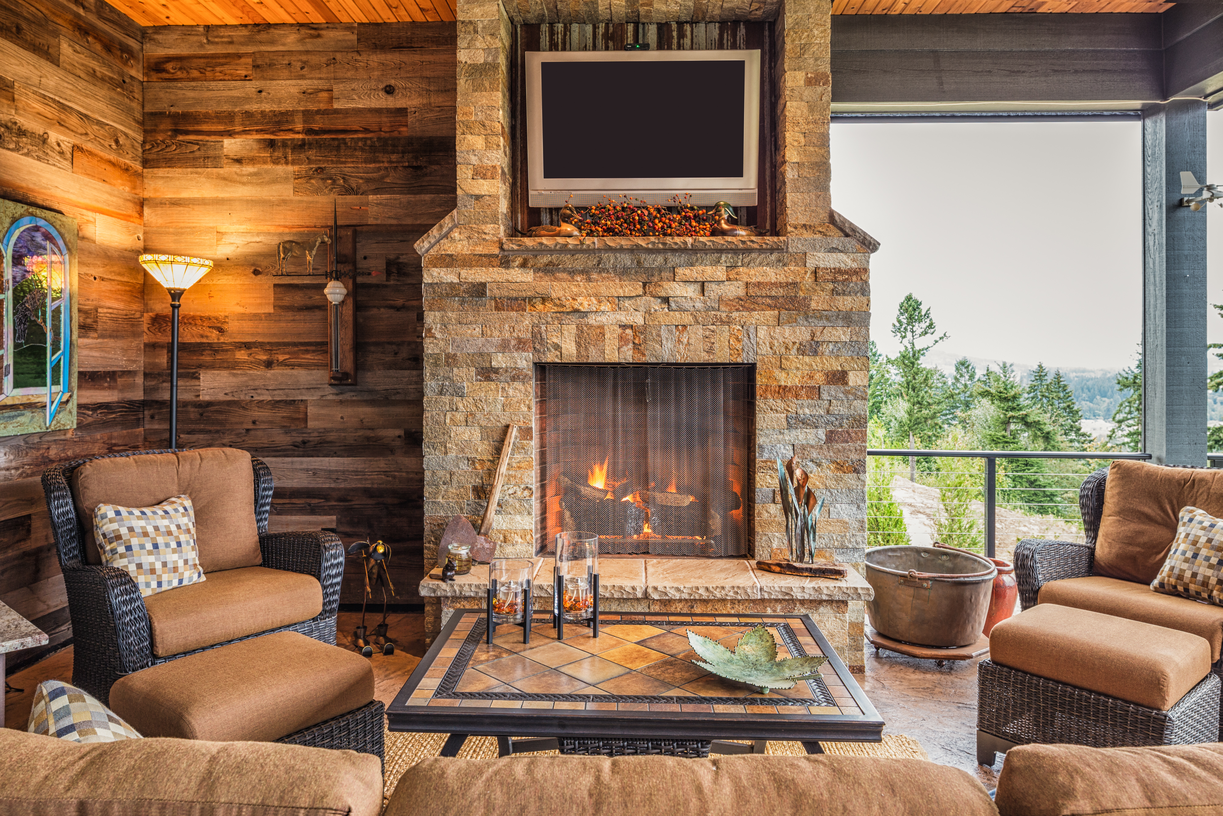 Covered Outdoor Patio Outside New Home with Couch, Chairs, TV, Fireplace, and Roaring Fire