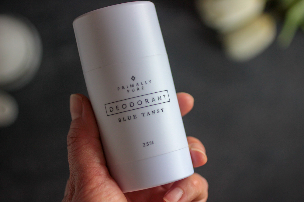 A woman's hand holding a natural non-toxic deodorant