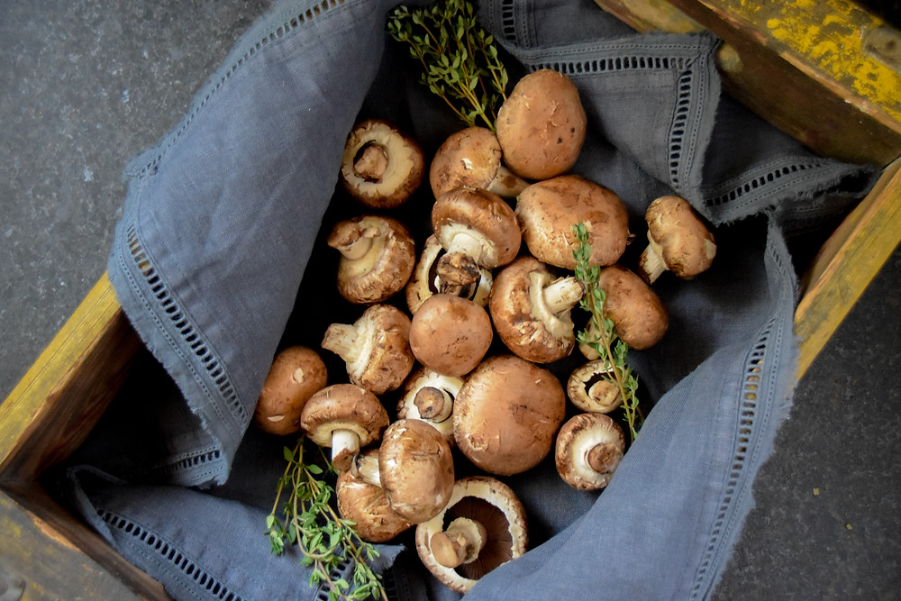 Mushrooms and thyme in a basket. Representing food for digestion and gut health