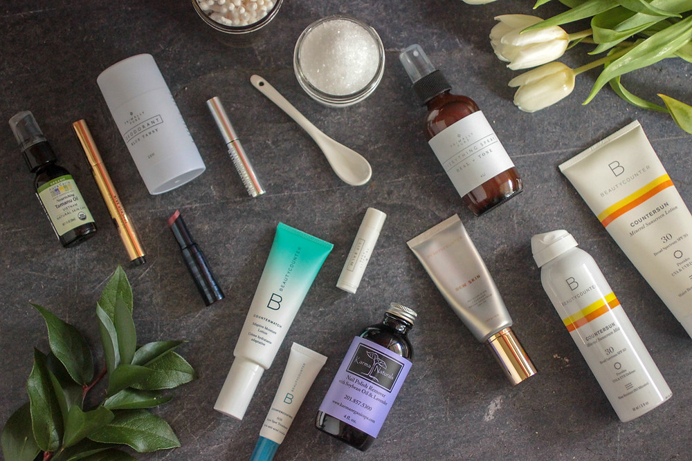 Safer non-toxic personal care products laid out on a slate surface