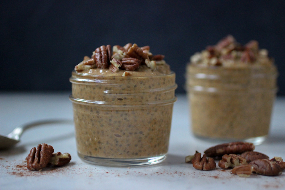 Two small mason jars of pumpkin chia pudding topped with chopped pecans