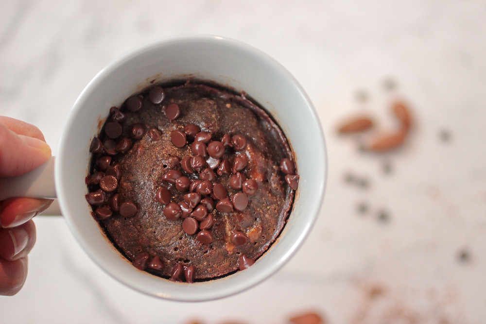 Birds eye view of chocolate almond butter brownie mug cake. Almonds and chocolate chips blurred in background