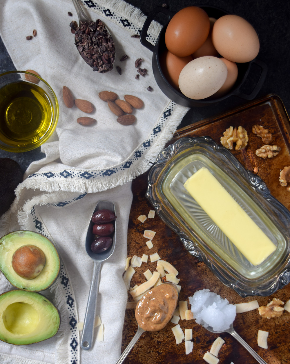 Healthy fats displayed together. Butter, eggs, avocado, nuts, oil