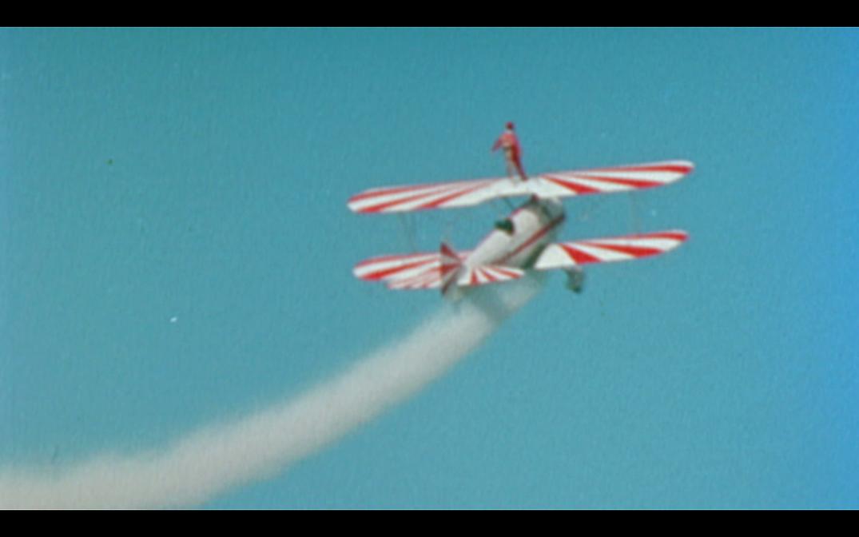 l'acrobate sur l'avion rouge et blanc