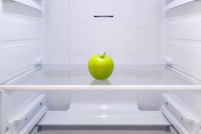 one green Apple on a shelf in an empty r