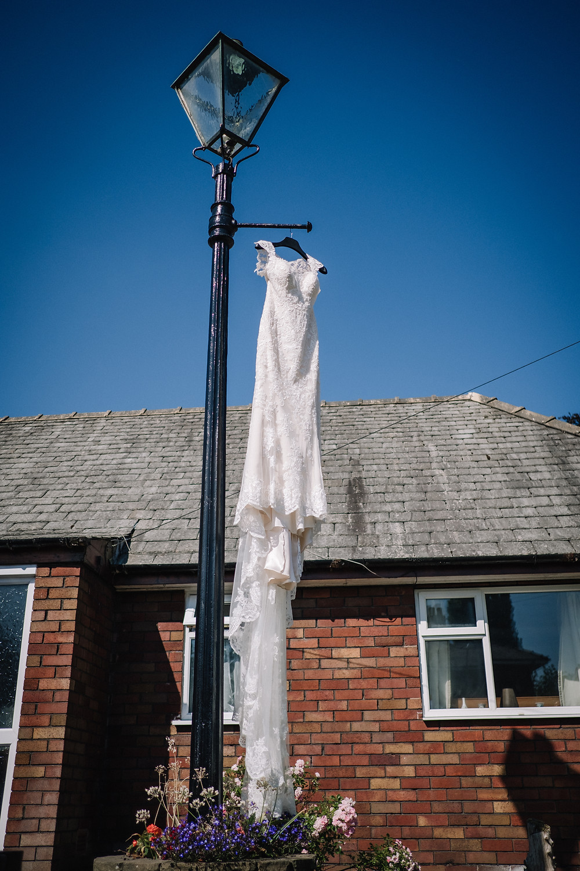 Wedding dress hanging from a vintage lamppost in a garden in Preston, Lancashire, United Kingdom