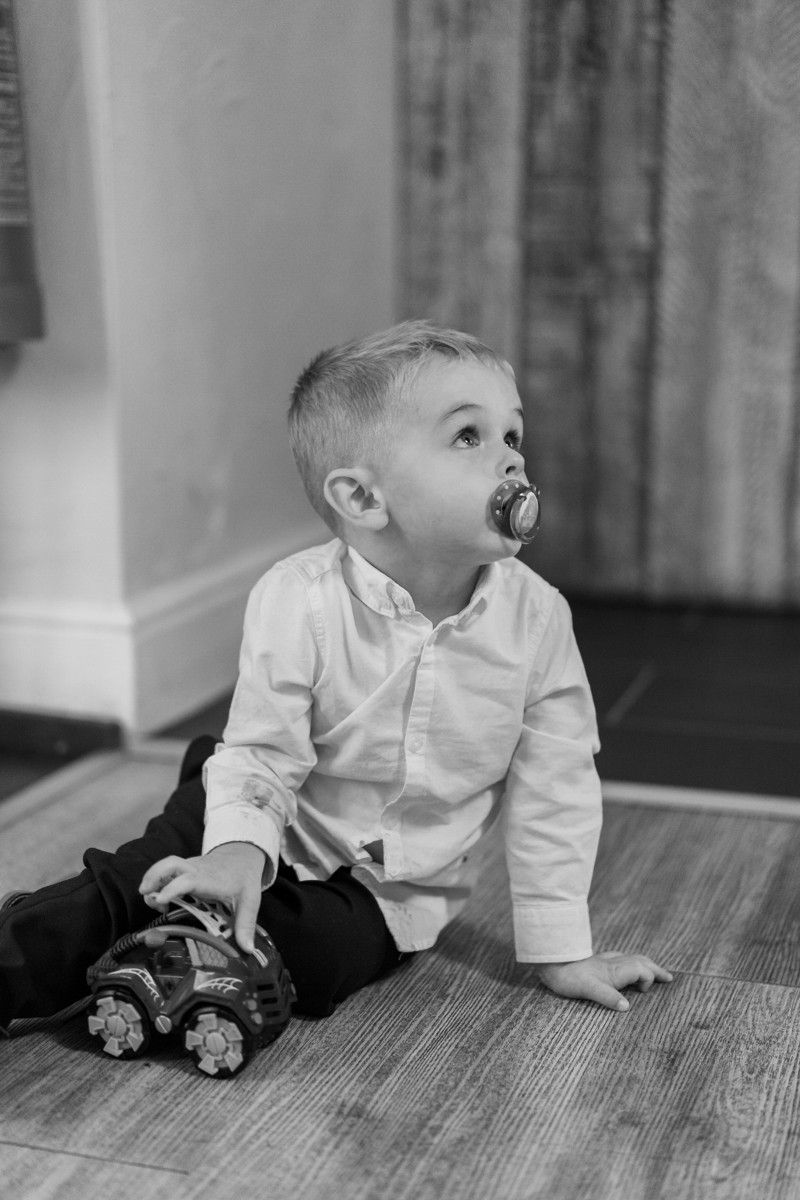 Wedding entertainment for children. A black and white professional wedding photograph of toddler playing with his toy car. Natural wedding photographer Leicestershire.