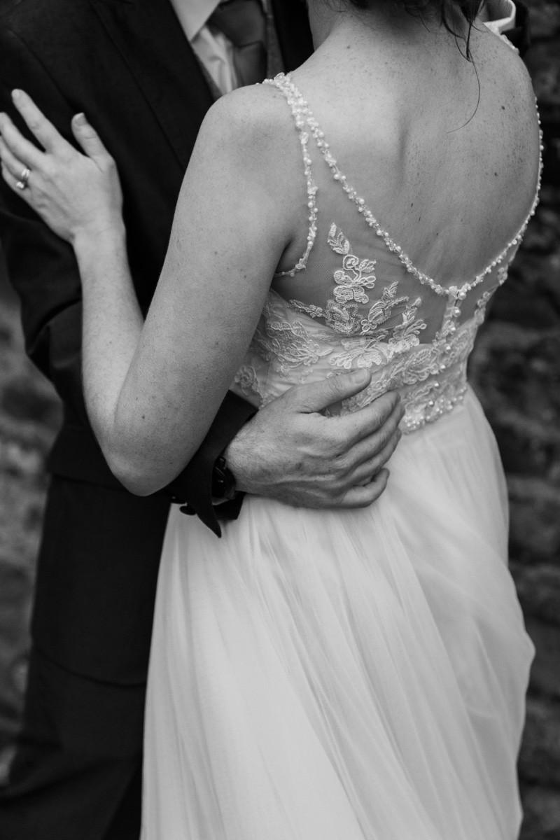 Documentary Wedding photography at Dodmoor House, Warwickshire. Wedding dress details as the happy couple embrace.