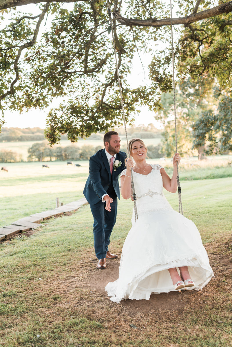 Laughing bride on a wedding venue swing in the Leicestershire countryside - pushed by dapper groom. Ashton Lodge Country House, Rugby. Countryside eco wedding.