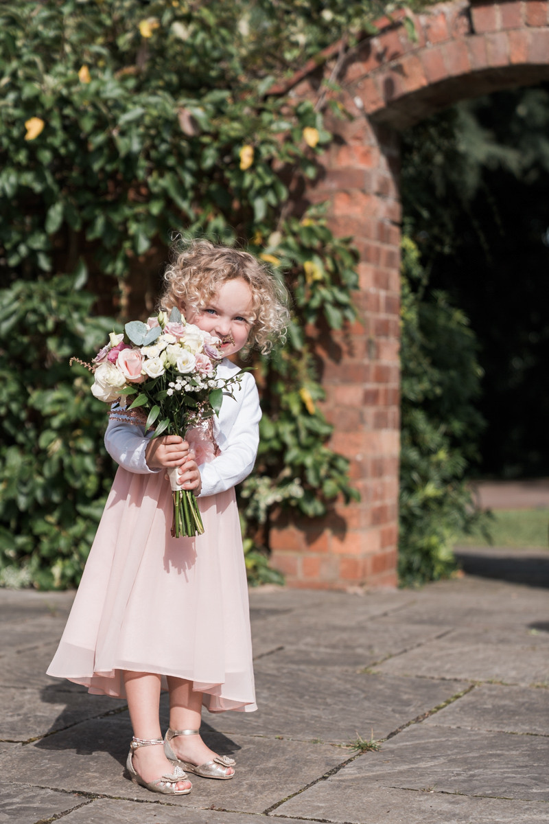 Outdoor wedding photography portrait of young girl with wedding bouquet. Archway in the background at Ashton Lodge, Leicestershire.
