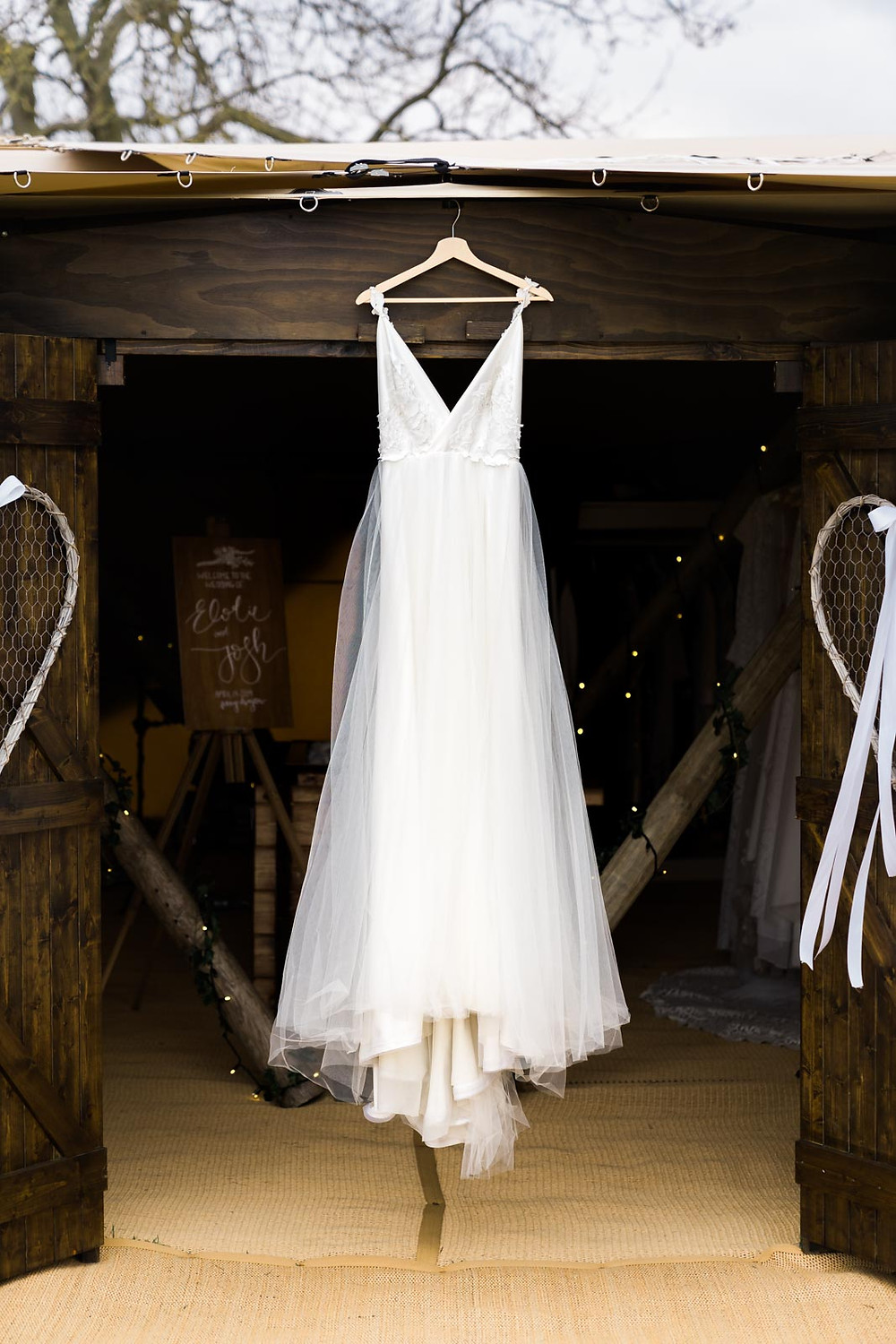 Full length white wedding dress hanging on tipi wedding venue in the Leicestershire countryside.