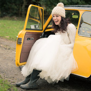 Documentary wedding photographer Derbyshire: Bride portrait in wedding dress and wellington boots. Sitting in Mini Cooper wedding car.