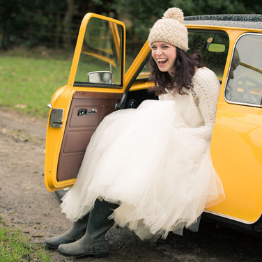 Documentary wedding photographer Derbyshire: Bride portrait in wedding dress and wellington boots. Sitting in Mini Cooper wedding car.