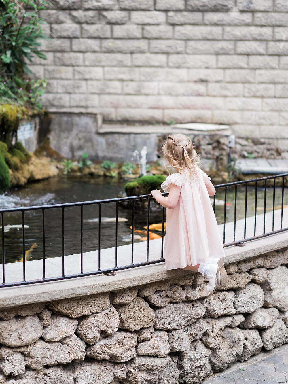 Wedding flower girl checking out the wedding venue fishpond in Matlock.