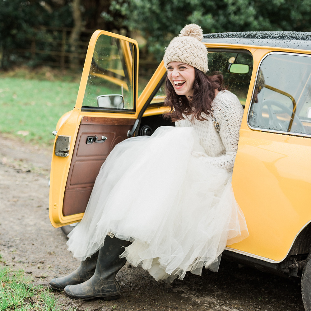 Boho wedding inspiration. Boho chic bride in wellies and a woolly hat stepping out of her yellow classic Mini Cooper wedding car. Countryside wedding photography Midlands